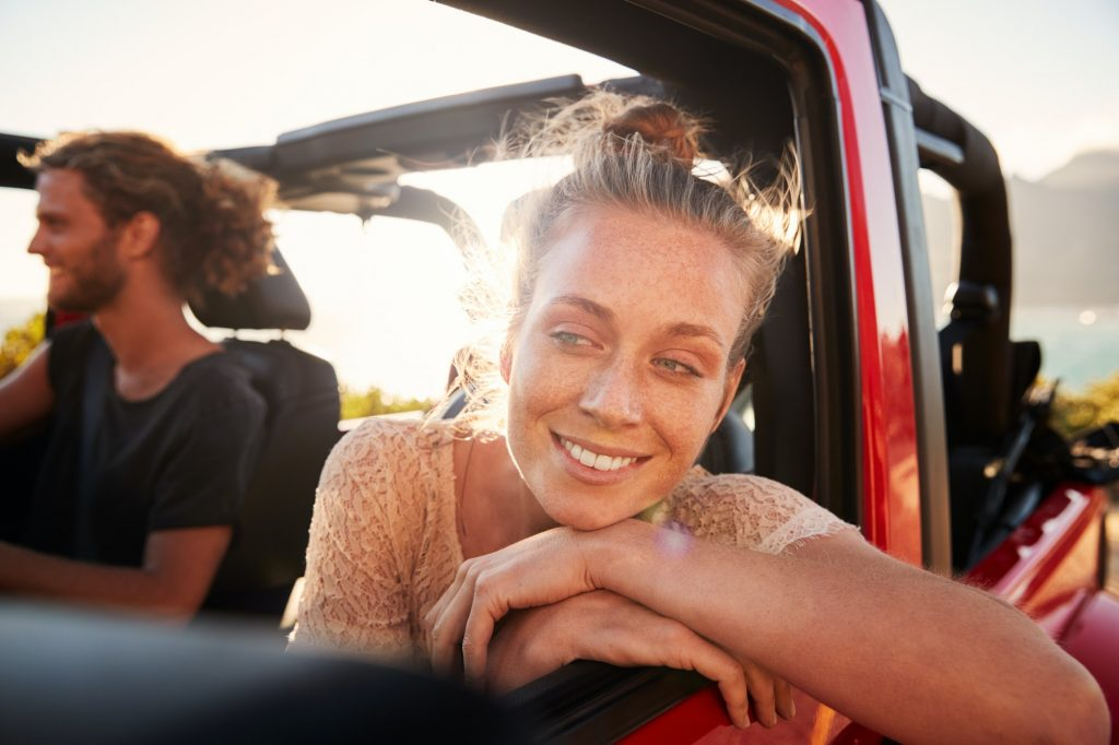 Millennial white couple on a road trip driving in open top car, women leaning on car door, close up for Smile Car Leasing